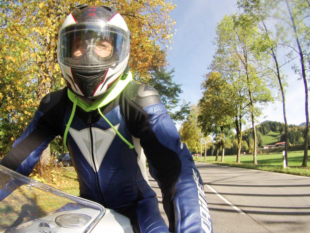 Motorradfahrer auf Allee in herbstlichen Farben.