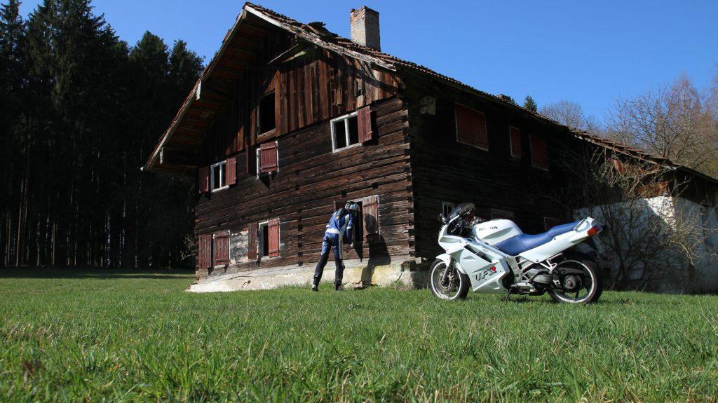 Motorrad vor Bauernhof Thomasbach. Der Fahrer schaut durchs Fenster.