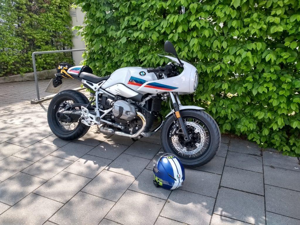 BMW R NineT Racer vor grüner Hecke
