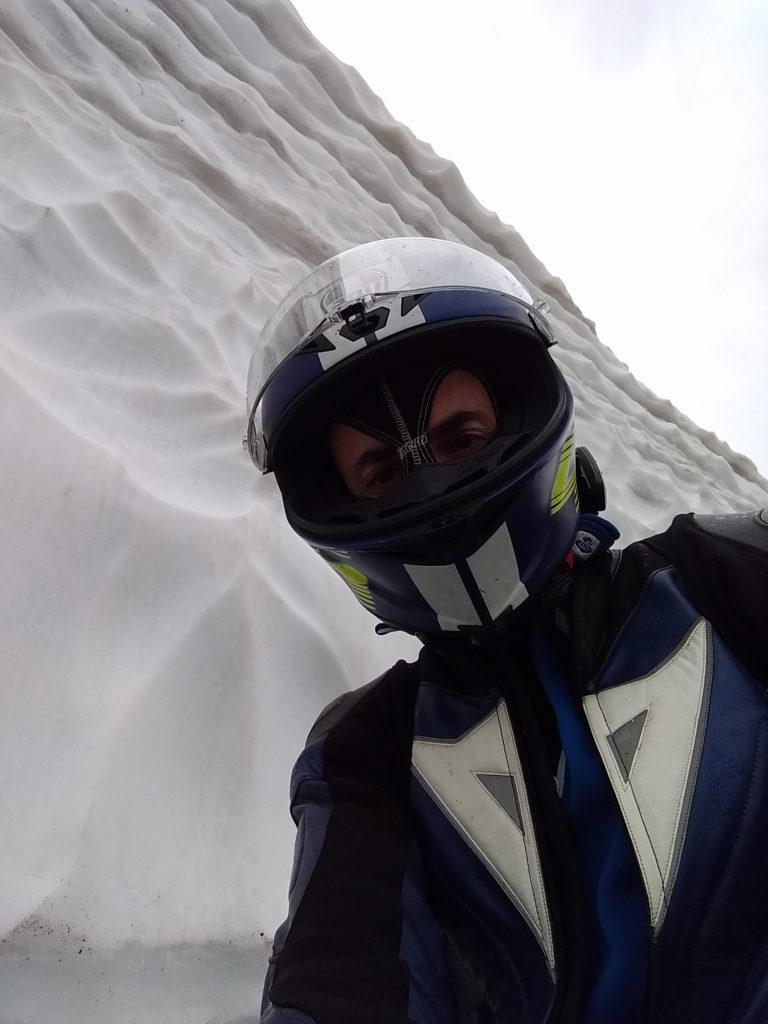 Motorradfahrer vor Schneewand