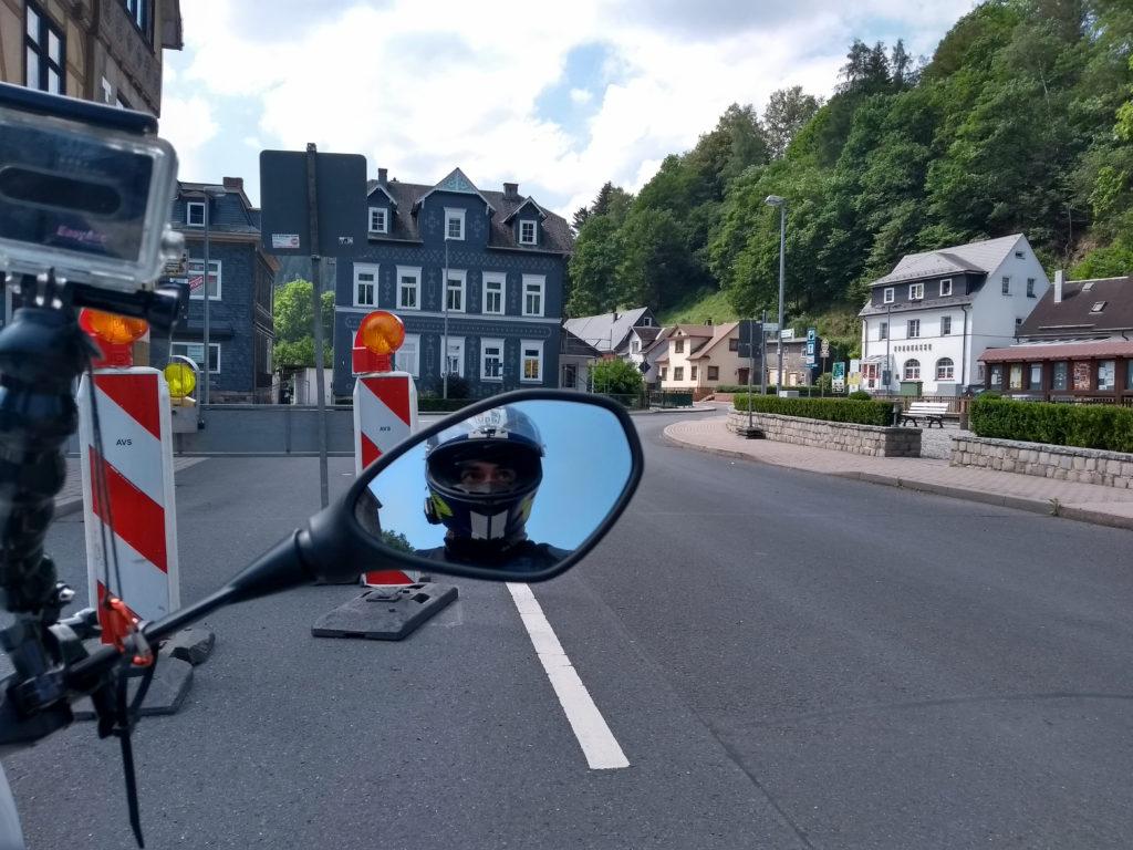 Motorradfahrer im Rückspiegel dahinter Baustelle