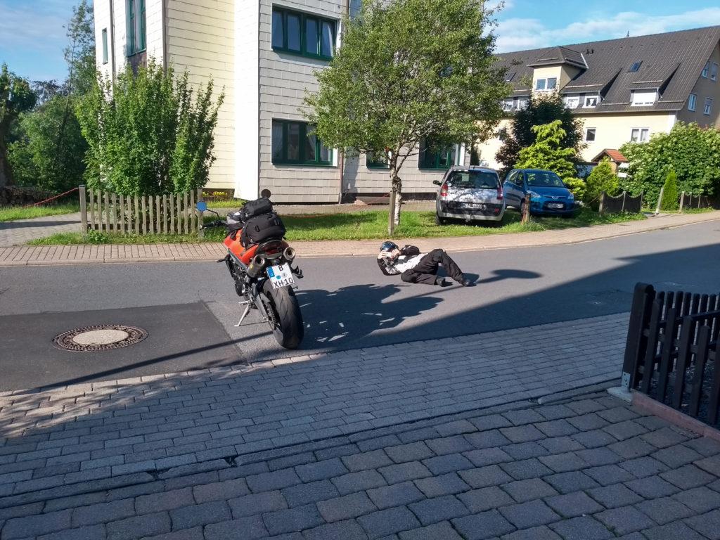 Motorradfahrer liegt fotografierend auf der Straße.