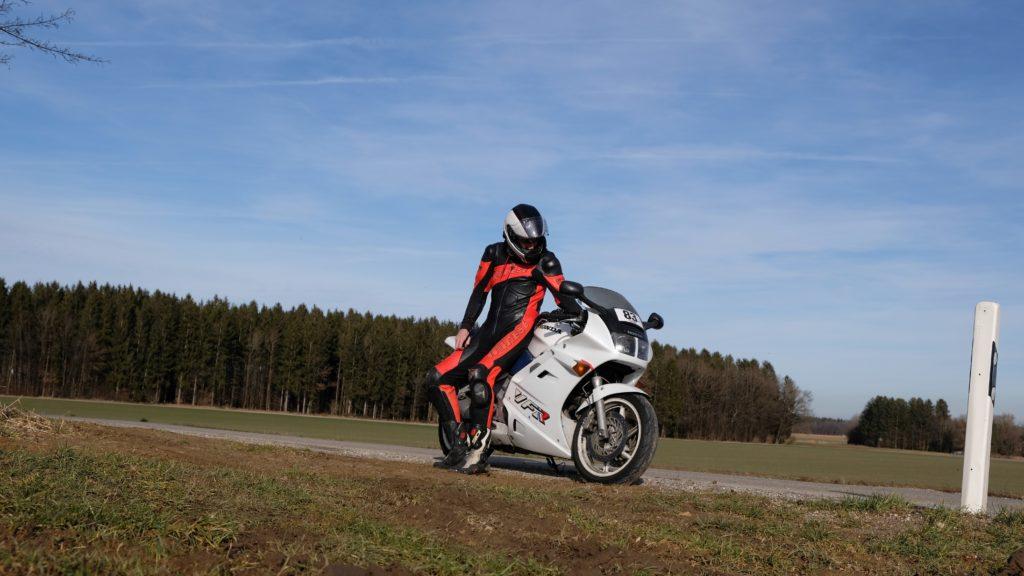 Motorradfahrer sitzt seitlich auf stehendem Motorrad